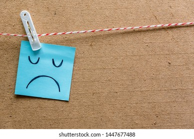 Unhappy boring moody emotion face pin on sticky note on cork board. Unhappy employee or demotivated at working place.