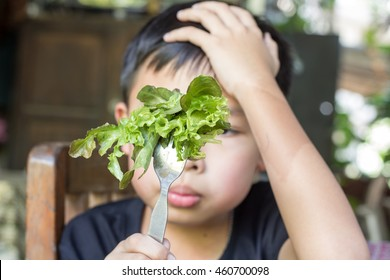 Unhappy boy does not want to eat healthy vegetables , refusing ,boring and ignored it.