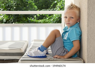 Unhappy boy sitting on balcony