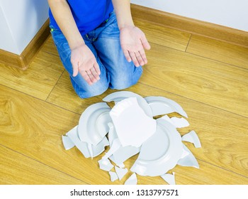 Unhappy boy sitting on floor with broken  plates. Child's guilt concept.