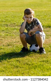 Unhappy boy sitting on a football. Lost a game concept