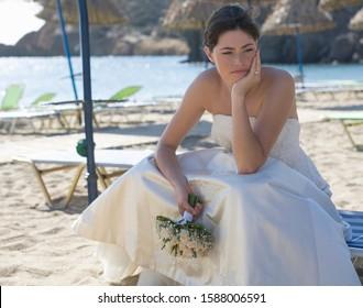 An unhappy bride sitting on a beach