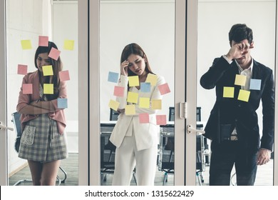 Unhappy business people feel disappointed while looking at sticky note on the windows in the office. Bankruptcy and failure concept.