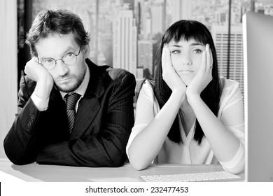 Unhappy business people sitting on desk depressed