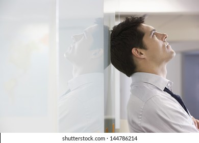 Unhappy businessman leaning back against office wall and looking at ceiling