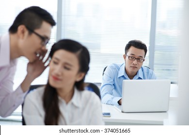 Unhappy businessman looking at gossiping colleagues
