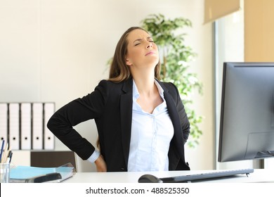 Unhappy businesswoman suffering back ache sitting on an uncomfortable seat at work indoors in her office