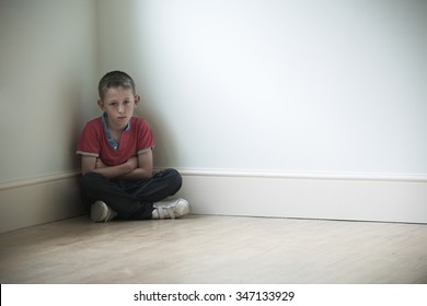 Unhappy Child Sitting In Corner Of Room