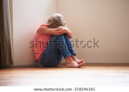 Unhappy Child Sitting On Floor In Corner At Home