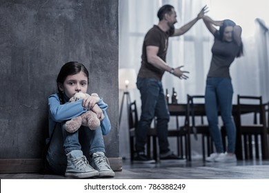 Unhappy childhood. Nice unhappy cheerless girl sitting on the floor and holding her toy while listening to her parents fight