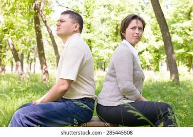 Unhappy couple in green summer park