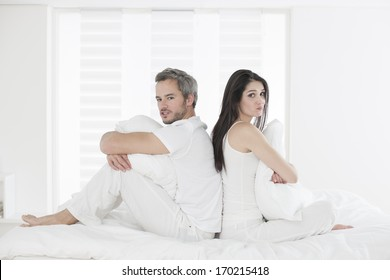 Unhappy couple ignoring each other sitting back to back on bed during a conflict