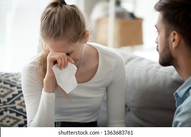 Unhappy couple sitting together on couch at home, woman with handkerchief crying, man looking at her, break up, interruption pregnancy, misunderstanding, relationships problem concept, close up