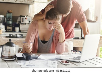 Unhappy couple unable to pay loan on time: stressed female doing paperwork sitting at table with laptop, papers, calculator and cell phone. Man trying to support his wife, patting her on head
