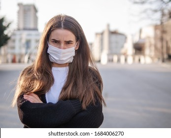 Unhappy cranky frustrated sick girl, brunette woman wearing surgery medical mask with arms crossed feeling bad, ill, being hit by coronavirus, Covid2019 standing outdoors in city looking at you camera