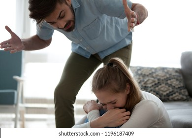 Unhappy crying frightened woman and aggressive man quarrelling at home. Angry husband emotionally arguing screaming shouting to scared wife psychological emotional abuse and domestic violence concept