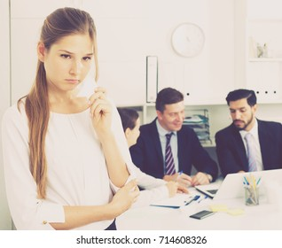 Unhappy and crying woman standing at office on background with coworkers