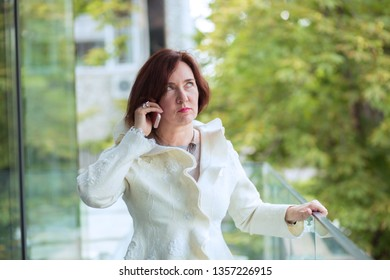 Unhappy customer. Closeup portrait headshot angry mature aged woman talking on mobile phone looking frustrated serious female green trees outdoor on background.