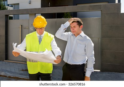 unhappy customer in stress and constructor foreman worker with helmet and vest arguing outdoors on new house building blueprints in real state business bankrupt and housing industry concept