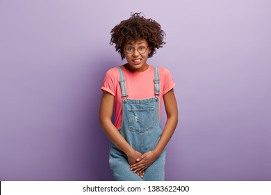 Unhappy dark skinned woman holds crotch, needs toilet, has problematic situation, wears pink t shirt and denim sarafan, suffers from cystitis, isolated over purple background. People and urgency