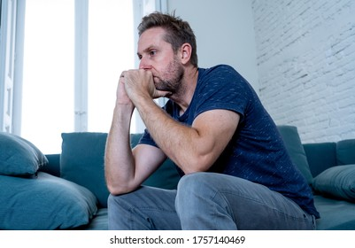 Unhappy depressed caucasian male crying in living room couch feeling desperate and lonely isolated at home. In stressed from work, unemployment, anxiety, heartbroken and depression concept