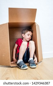unhappy depressed child sitting in a box, seeking for protection and refuge from mistreatment in his cardboard home