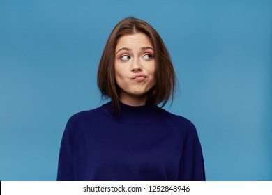 Unhappy depressed cute young woman in dark blue pellover, frowning her face and looking to the side. isolated over blue background. Female thinking about difficult situation in her life