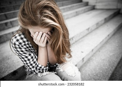 Unhappy depressed teenager with face in hands sitting outdoor