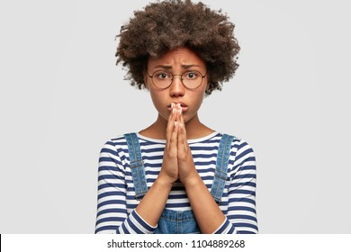 Unhappy despondent female asks for apologize and forgiveness, has miserable expression, makes pleading gesture, hopes for something good, stands against white background. Young woman begs indoor.