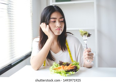 The unhappy dieting Asian girl has a boring expression when she eats vegetables. She have sad face. diet, clean food, Healthy food and vegan concept.