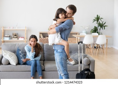 Unhappy diverse family in living room at home. Sad father hugs hold on hand small daughter, mother sitting on sofa. Parents divorcing, child stay with mommy dad leave with suitcase. Break up concept