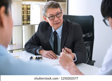 Unhappy divorce couple having conflict, husband and wife during divorce process with senior male lawyer or counselor and couple signing decree of divorce contract in lawyer's office.