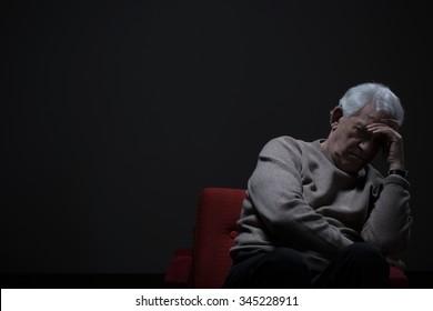 Unhappy elder man sitting alone in darkness