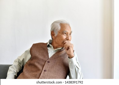 Unhappy elderly asian man with carefully thought gesture, Lonely old man looking out the window worry about life problem, Senior healthcare concept.
