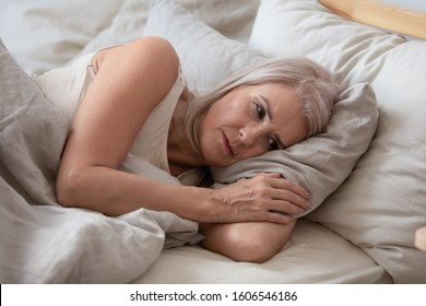 Unhappy elderly woman lying in bed at home thinking pondering over life problems, mourning or yearning, upset sad senior female relax in bedroom feel unwell or stressed suffering from insomnia