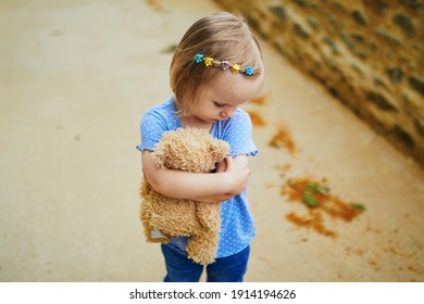 Unhappy and emotional toddler girl with teddy bear outdoors. Misbehaving child on the street. Terrible twos and kid tantrums concept