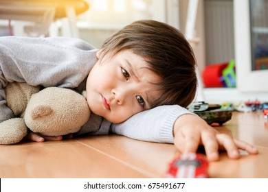 Unhappy face of Toddler boy lying down on wooden floor with his teddy bear at home