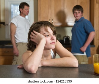 Unhappy family: father and older brother look on as younger brother looks annoyed, tired, bored.