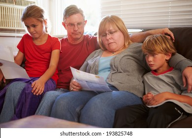 Unhappy Family Sitting On Sofa Looking At Bills