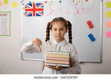 Unhappy female learner of secondary school showing thumbs down gesture, having no desire to study in school