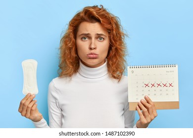 Unhappy ginger woman purses lower lip, holds periods calendar and sanitary pad, upset to have menses cramps, cares about hygiene, wears casual outfit, isolated on blue wall. Good protection.