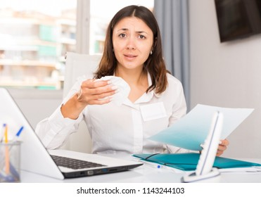 Unhappy girl manager reading documents and holding napkin  in office