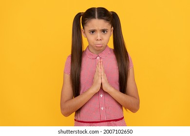 Unhappy girl prayer plead holding palms together in prayer gesture yellow background, pleading