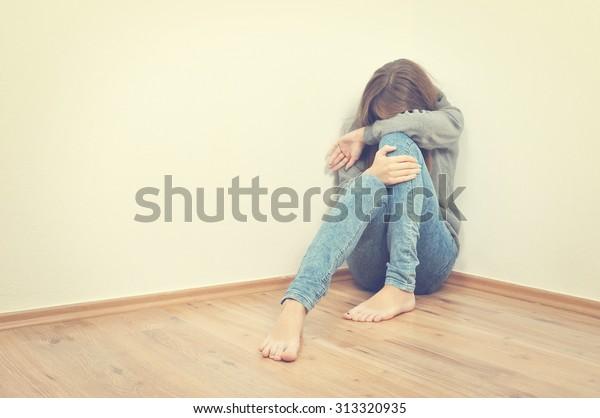 Unhappy girl sitting in a corner