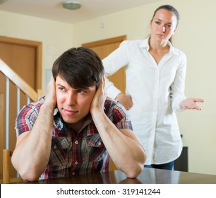 Unhappy guy and sad woman during conflict in living room at home
