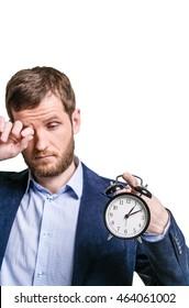 Unhappy with the half asleep man holding a ringing alarm clock, morning awakening, closeup portraits
