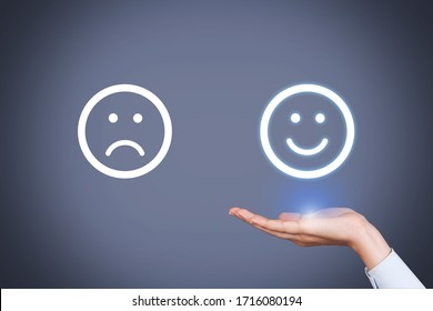 Unhappy and Happy Smileys on Human Hand