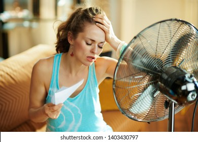 unhappy housewife in the modern house in sunny hot summer day in the front of working fan suffering from summer heat