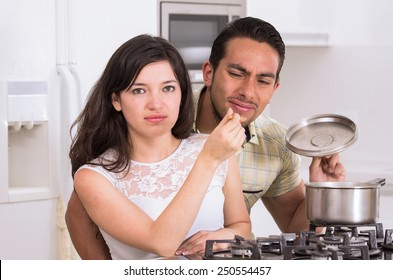 unhappy husband trying unpleasant food that his wife prepared