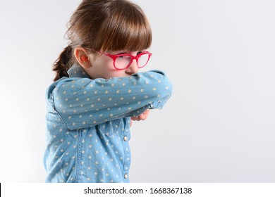 Unhappy kid Cough into her elbow, not her hand. Small girl pull the collar of her T-shirt up to cover mouth when coughing. Coughing advice from experts who seek to minimize risk of viral transmission